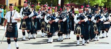 Marching band with men in kilts playing bagpipes
